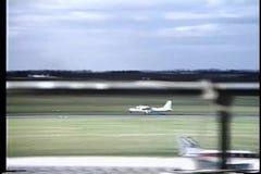 Rear view two men watching propeller plane take off stock footage