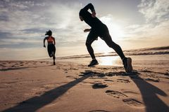 Fit people sprinting on the beach. Rear view of two people sprinting on the beach. Man and women doing running training on the shore in morning Stock Photography