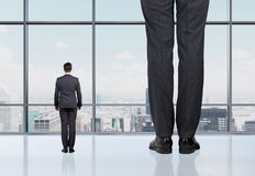 Rear view of two professionals in formal suites who stand in front of panoramic window Royalty Free Stock Photography