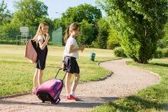 Rear view of two schoolgirl girlfriends elementary school students walking with school bag in the yard.  Stock Photo
