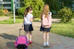 Rear view of two schoolgirl girlfriends elementary school students walking with school bag in the yard.  Stock Photos