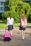Rear view of two schoolgirl girlfriends elementary school students walking with school bag in the yard.  royalty free stock image