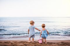 Rear view of two toddler children playing on sand beach on summer holiday. A rear view of two toddler children playing on sand beach on summer family holiday stock photo