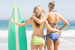 Rear view of two women in bikini standing with a surfboard on the beach Stock Photo
