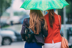 Rear view of two women friends walking under umbrella Stock Photography