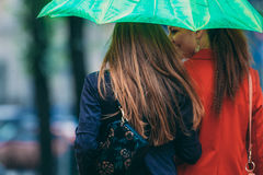 Rear view of two women friends walking under umbrella Royalty Free Stock Photo