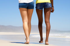 Rear view two women walking barefoot on beach Stock Images
