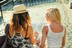 Rear view of two young women with city map in search of attractions. Young tourist girls friends traveling on holidays. Royalty Free Stock Photos