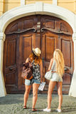 Rear view of two young women with city map in search of attractions. Young tourist girls friends traveling on holidays. Summer vac Stock Image