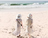 Rear view of two young women in long dresses and hats walking along sandy beach royalty free stock images