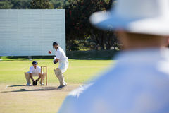 Rear view of umpire standing at cricket match field. On sunny day stock photography