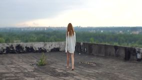 Rear view of the unknown mad woman with red hair in white shirt walking along the roof of the mental hospital. Rear view of the unknown mad woman with red hair stock video footage