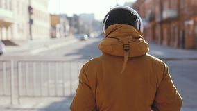 Rear view, man listening music in headphones outdoors, video included original audio. Rear view, unrecognizable man listening music in headphones outdoors, video stock video footage