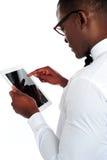Rear-view van Afrikaan die een aanraking-stootkussen apparaat houdt stock afbeeldingen