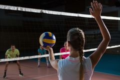 Rear view of volleyball player playing with teammates. Rear view of female volleyball player playing with teammates at court Stock Photography