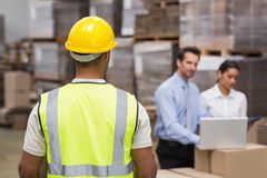 Rear view of warehouse worker in front of his managers stock image