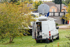Rear view of white Tv Television Trucks with multiple Satellite. Parabolic antennas and fiber optic cables going inside reporting live the official French Stock Photos