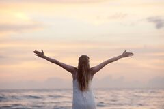 Rear View of Woman With Arms Raised at Beach during Sunset Royalty Free Stock Image