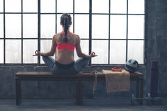 Rear view of woman on bench in lotus position in loft gym Stock Images