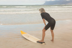 Rear view of woman bending by surfboard while standing on shore. At beach Royalty Free Stock Photo