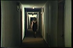 Rear view of woman in black dress walking down hotel corridor