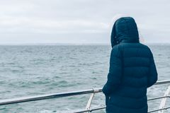 Rear view woman in blue down coat and hood. Looking at ocean on grey winter day. Female stands on seafront near railing holding her hands in pockets Stock Images