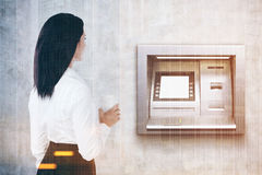 Rear view of woman with coffee, atm machine toned Royalty Free Stock Image