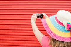 Back view of young female taking self portrait with vintage film camera on red background. royalty free stock photo