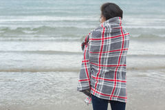 Rear view of woman covered with blanket looking at sea on beach Stock Photo