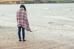 Rear view of woman covered with blanket looking at sea on beach Royalty Free Stock Image