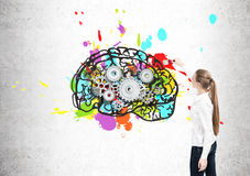 Rear view of woman drawing brain, cogs. Rear view of a blond woman painting a bright and colorful brain sketch on a concrete wall. There are cogs inside it Stock Image