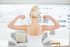 Rear view of woman flexing muscles in fitness studio Stock Photo