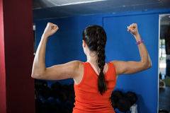 Rear view of woman flexing muscles in gym. Rear view of woman flexing muscles while standing in gym Stock Images