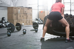 Rear view of woman flipping tire in crossfit gym. Rear view of women flipping tire in crossfit gym Stock Image