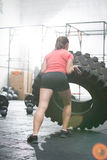 Rear view of woman flipping tire in gym Royalty Free Stock Photo