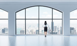 Rear view of a woman in formal clothes who is looking out the window in a modern clean interior with huge panoramic windows. New Y. Ork city view royalty free illustration