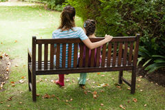 Rear view of woman and girl sitting on wooden bench Royalty Free Stock Images