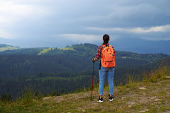 Woman with hiking poles standing on edge of mountain Stock Photo
