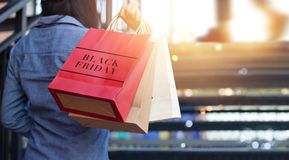Rear view of woman holding Black Friday shopping bag. While on up stairs outdoors on the mall background royalty free stock image