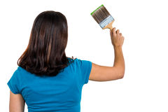 Rear view of woman holding paint brush Stock Image