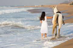 Rear view woman horse beach. Rear view of young woman walking a white horse on beach Royalty Free Stock Image