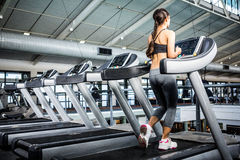 Rear view of woman jogging in treadmill Stock Photos
