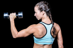 Rear view of woman lifting dumbbell Stock Image