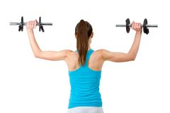 Rear view of woman lifting weights. Royalty Free Stock Image