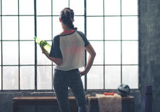 Rear view of woman looking out of loft gym holding water bottle Royalty Free Stock Photos
