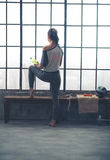Rear view of woman looking out window holding water in loft gym Stock Photo