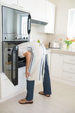 Rear view of woman looking into the oven in kitchen Stock Image