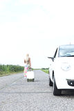 Rear view of woman with luggage leaving broken down car on country road. Rear view of women with luggage leaving broken down car on country road Stock Photography