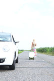 Rear view of woman with luggage leaving broken down car on country road Royalty Free Stock Photo
