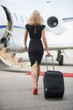 Rear View Of Woman With Luggage Walking Towards. Full length rear view of wealthy woman with luggage walking towards private jet at airport terminal Stock Image